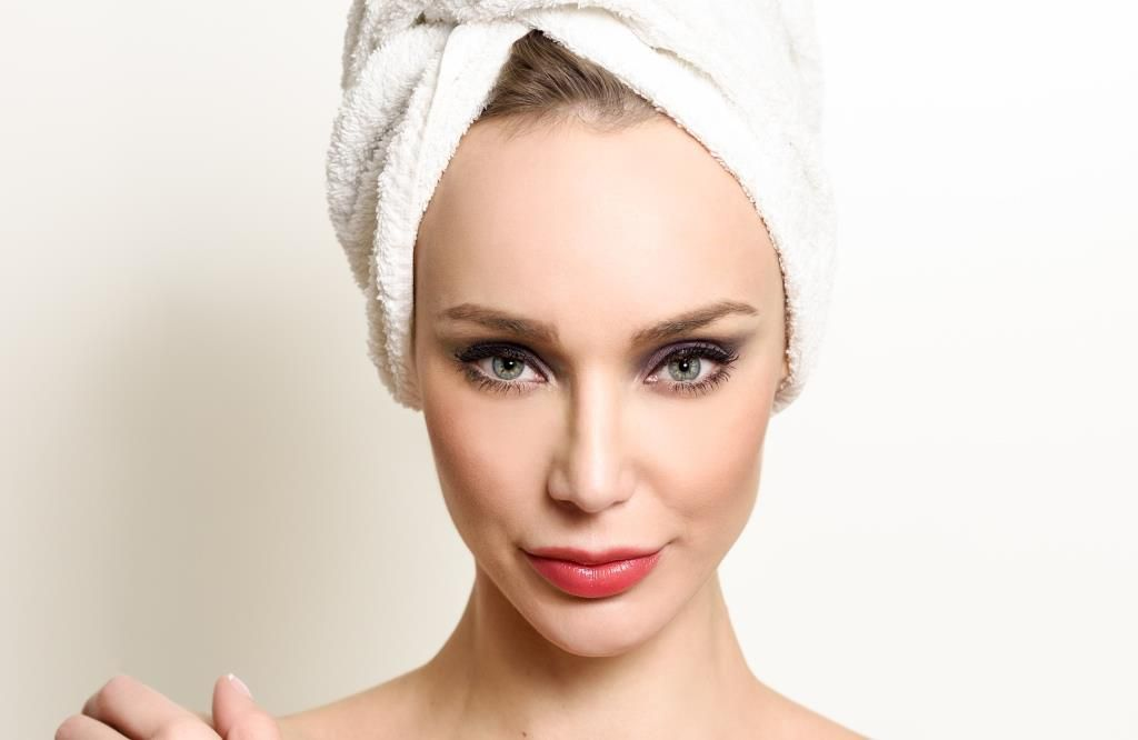 Beautiful blond woman with white towel on her head.